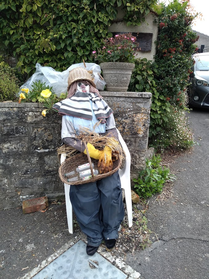 Scarecrow with a basket of empty drink bottles
